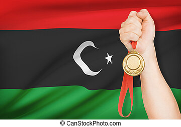 Medal in hand with flag on background - State of Libya -...
