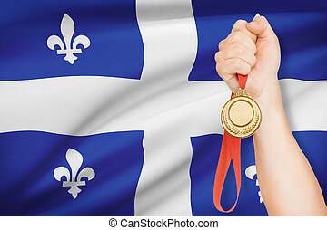 Medal in hand with flag on background - Quebec - Sportsman...