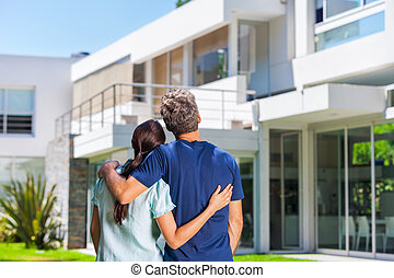 Family in big house - couple embracing in front of new big...