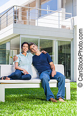 Family in big house - couple sitting in front of big modern...