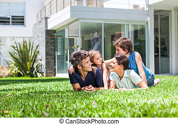 Family in big house - happy family lying on grass in front...