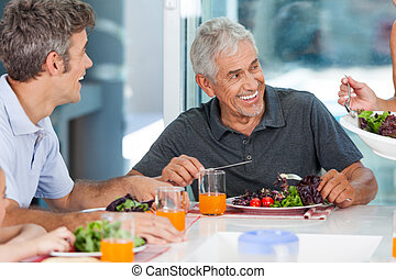 mature man with family dinner table - mature man with family...
