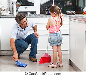 Father and daughter cleaning in the kitchen, sweep floor at...