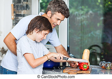 father and son cooking home kitchen, slicing