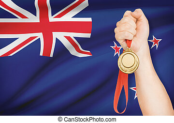 Medal in hand with flag on background - New Zealand -...