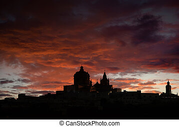 Mdina - medieval city of Malta in silhouette at sunset