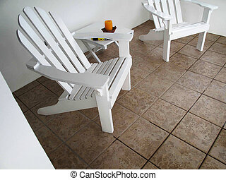White Patio Chairs - Two white patio chairs sit in the shade...