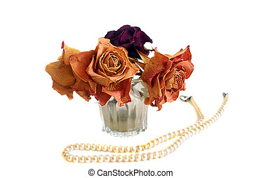 Composition of three dried roses and string of pearls