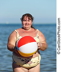overweight woman with ball on beach near sea