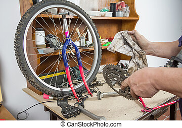 Hands of bicycle mechanic cleaning chainring bike - Hands of...
