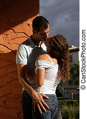 beautiful sexy young lovers kissing in the hot afternoon sun up against a wall in romantic tropical setting with heavy shadows and vibrant colors