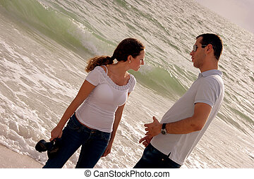 beautiful young couple talking in front of the ocean