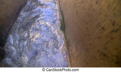 sewer drains flow down on a trench - dirty water from the...