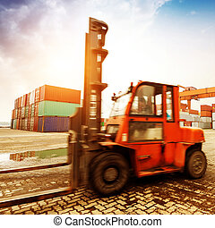 forklift handling the container box at dockyard with...