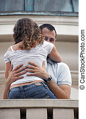 man holding woman looking over shoulder at viewer
