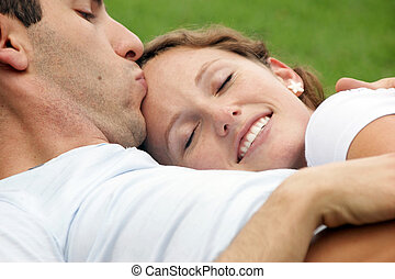 smiling woman being kissed on forehead by husband - smiling...