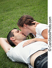 sweet image of young couple kissing  on the grass