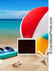 photoframe and beach gear on the sea sand