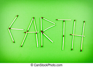 Word EARTH made of matchsticks isolated on green background.