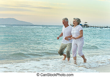 Nice old couple at resort - Nice old couple running on sea...