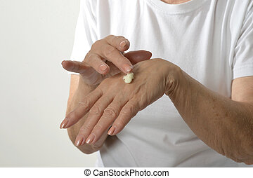 Older woman applying cream on hands closeup on white...