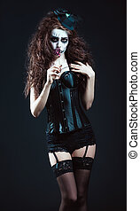 Young woman in the image of sad gothic freak clown smelling...