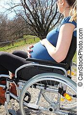 Schwangere Frau im Rollstuhl im Park
