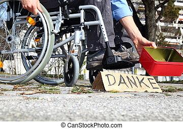 Bedrftiger Rollstuhlfahrer mit DANKE Schild