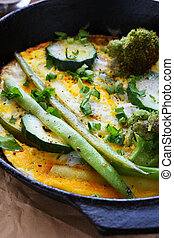 roasted vegetables and scrambled eggs in a frying pan, food...