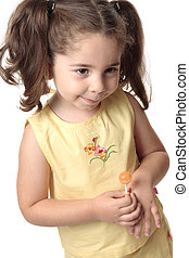 Shy toddler girl smiling - A toddler girl dressed in a...