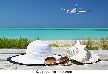 Sunglasses, hat and shell against ocean Exuma, Bahamas