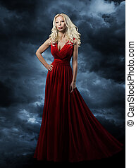 Woman in red dress, long hair blonde in fashion evening gown over sky background, hand on hip