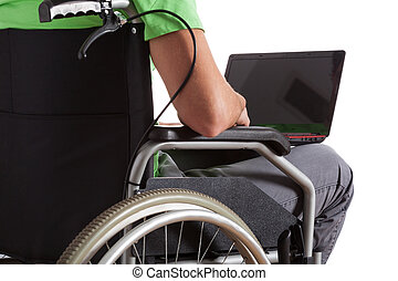 Paralyzed teenager with laptop on his knees