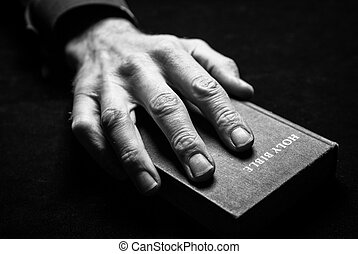 A mans hand holding the Holy Bible.