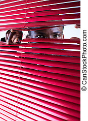 red blinds - afro-american businessman glancing through red...