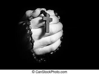 Praying hands - Hands holding onto rosary beads and cross...