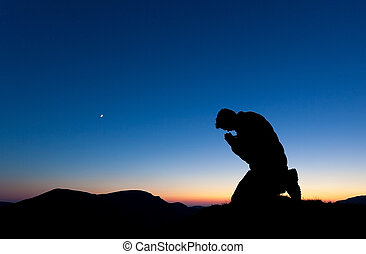 Man Praying - Man praying on the summit of a mountain at sun...