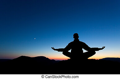 Meditation - A man is meditating, in prayer on the summit of...