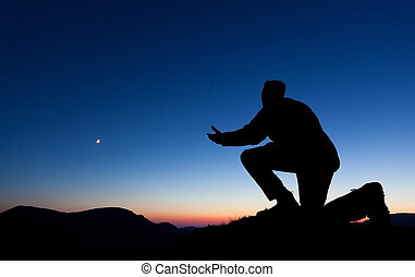 Man Praying - Man praying for forgiveness on the summit of a...