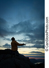 Man Pleading - A man pleading to God on the summit of a...
