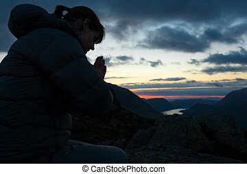 Woman Praying - A woman praying to God on the summit of a...