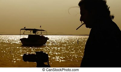 Man smoking and taking photo near the sea