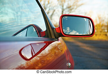 Wing Mirror - The wing mirror of a red car at sunset