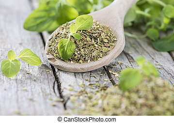 Oregano on a wooden spoon (against wooden background)