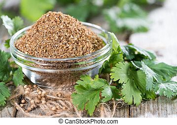 Portion of rubbed Coriander (close-up shot) on wooden...