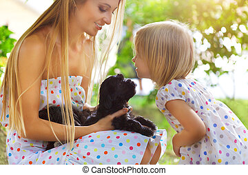 Cute little girl and her mother hugging dog puppies...