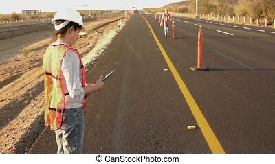Road Worker Foreman Calling Laborer - A female road...