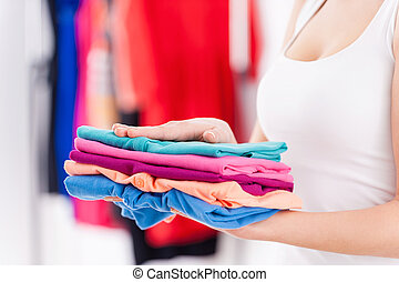 Stack of colorful clothes Cropped image of woman holding...