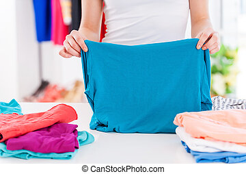 Folding clothes Cropped image of woman folding clothes on...