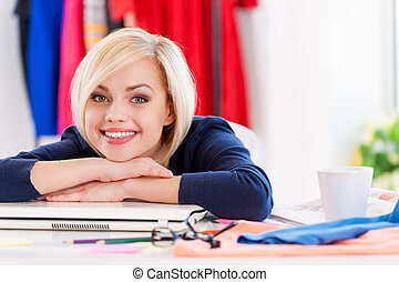 Confident and creative businesswoman. Beautiful young woman holding hands on chin and smiling while sitting at her working place